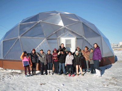 Ben Canning poses with students from the local community in front of completed greenhouse.